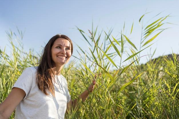 Smiley-frau, die durch pflanzen mit kopienraum geht