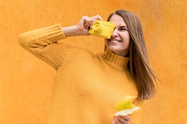 Smiley-frau, die ein auge mit einem herbstblatt bedeckt