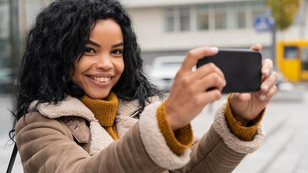 Smiley-frau, die ein selfie mit ihrem smartphone nimmt