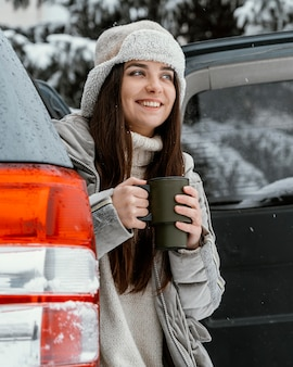 Smiley-frau, die ein warmes getränk während eines straßenausfluges hat