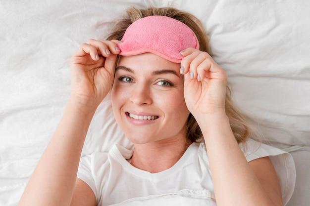 Smiley-frau, die eine schlafmaske trägt