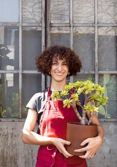 Smiley-frau, die eine schöne pflanze hält