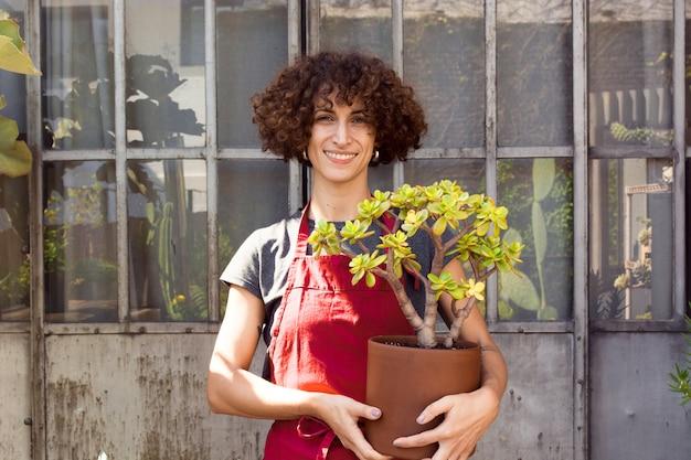 Smiley-frau, die eine schöne pflanze im topf hält