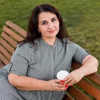 Smiley-frau, die eine tasse kaffee hält, während sie auf einer bank sitzt