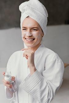 Smiley-frau, die eine weiße gesichtscreme verwendet
