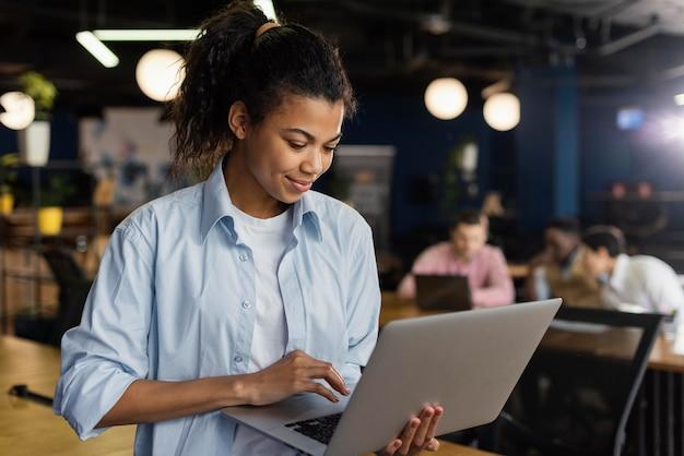 Smiley-frau, die einen laptop im büro hält und arbeitet