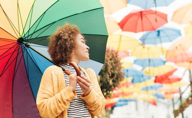 Smiley-frau, die einen regenbogenschirm mit kopienraum hält