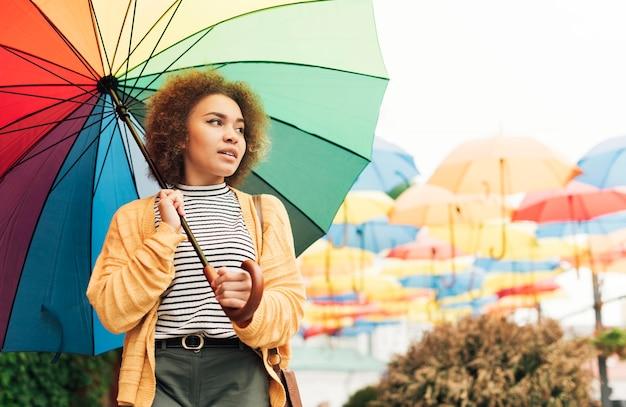 Smiley-frau, die einen spaziergang im freien mit einem regenbogenschirm nimmt