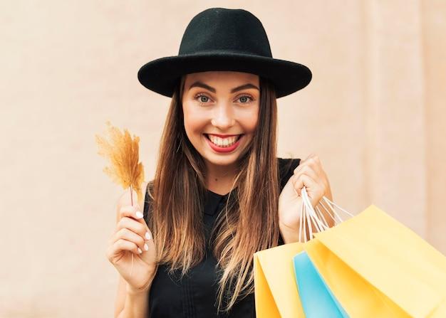 Smiley-frau, die einkaufstaschen hält