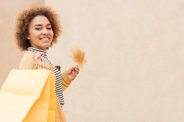 Smiley-frau, die einkaufstaschen mit kopienraum hält