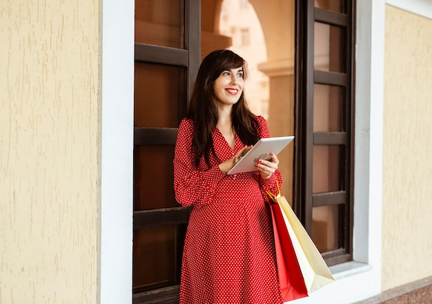 Smiley-frau, die einkaufstaschen und tablette hält
