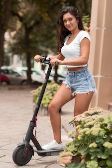 Smiley-frau, die elektroroller im freien reitet