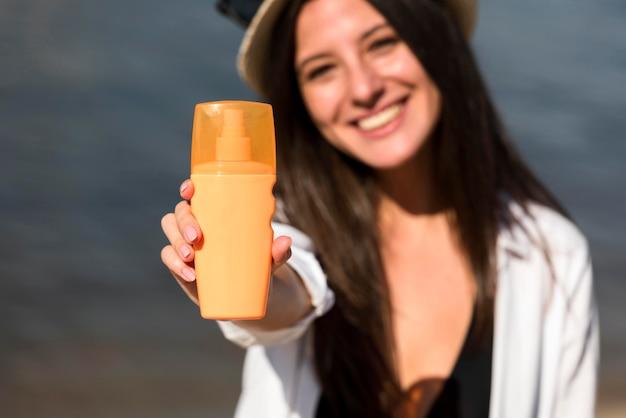 Smiley-frau, die flasche sonnenschutz am strand hält