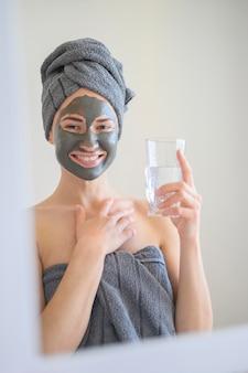 Smiley-frau, die gesichtsmaske trägt und glas wasser hält