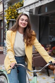 Smiley-frau, die ihr fahrrad auf der straße reitet