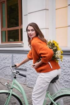 Smiley-frau, die ihr fahrrad draußen mit blumen reitet