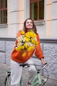 Smiley-frau, die ihr fahrrad draußen mit blumenstrauß reitet