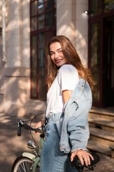 Smiley-frau, die ihr fahrrad in der stadt reitet