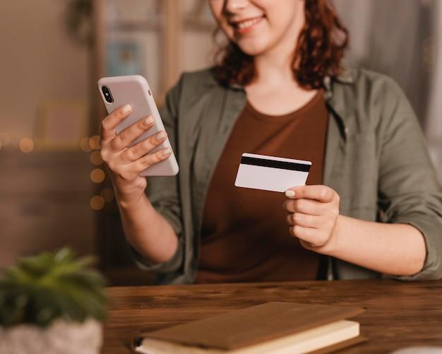 Smiley-frau, die ihr smartphone mit kreditkarte zu hause benutzt