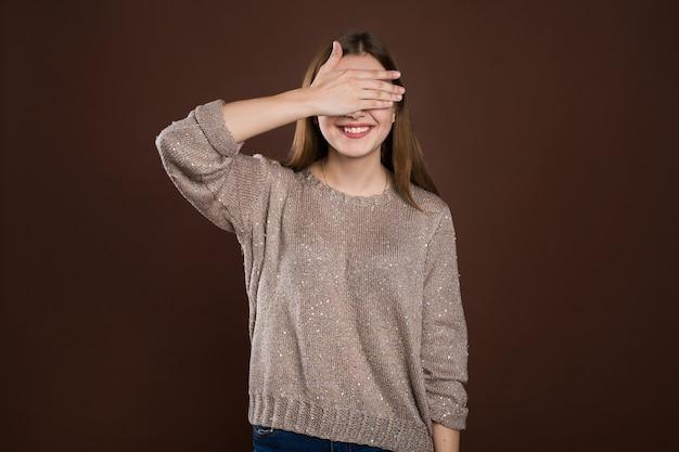Smiley-frau, die ihre augen durch hände über braunem hintergrund bedeckt