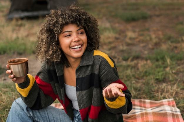 Smiley-frau, die ihre zeit im freien beim zelten genießt