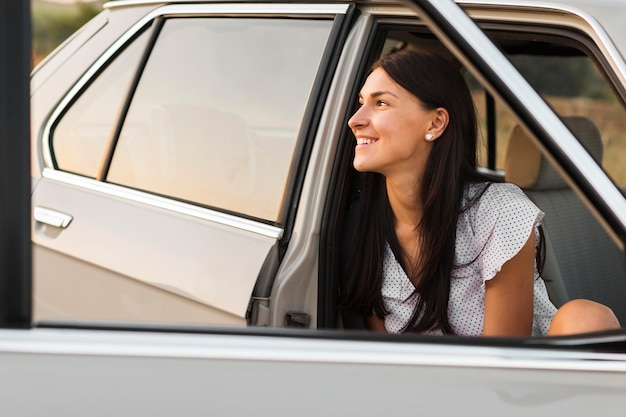 Smiley-frau, die im auto aufwirft