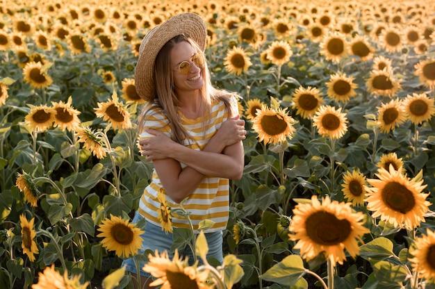 Smiley-frau, die im sonnenblumenfeld aufwirft