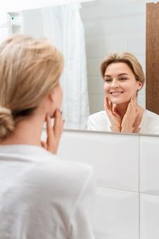 Smiley-frau, die in den spiegel schaut