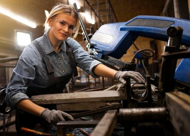 Smiley-frau, die in der fabrik arbeitet