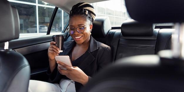 Smiley-frau, die kaffee trinkt und smartphone von ihrem auto betrachtet
