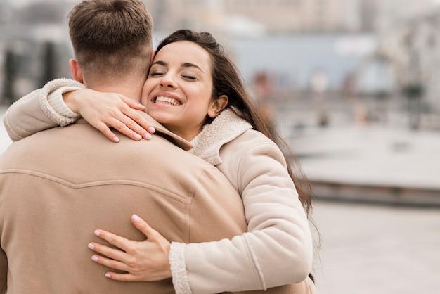 Smiley-frau, die mann draußen umarmt