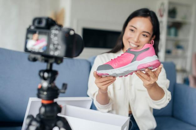 Smiley-frau, die mit ihren sportschuhen vloggt