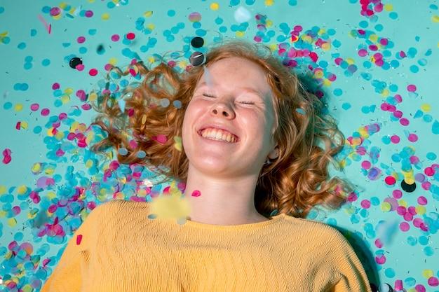 Smiley-frau, die mit konfetti um sie herum auf dem boden liegt