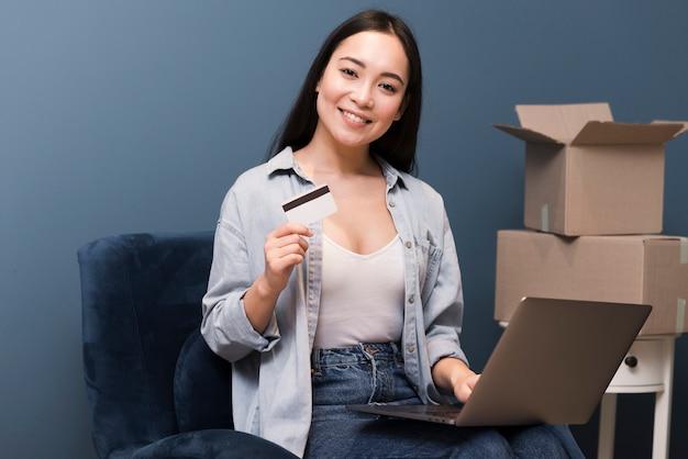 Smiley-frau, die mit kreditkarte und laptop neben kisten aufwirft