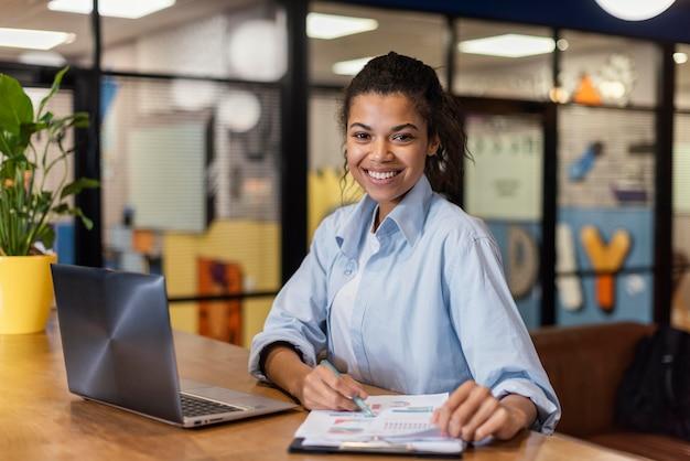 Smiley-frau, die mit laptop und papieren im büro arbeitet