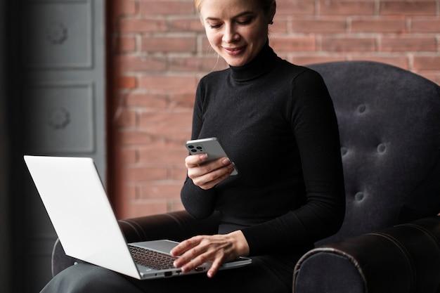 Smiley-frau, die mit laptop und smartphone arbeitet