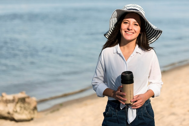 Smiley-frau, die mit thermoskanne am strand aufwirft