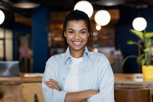 Smiley-frau, die mit verschränkten armen am arbeitsplatz aufwirft