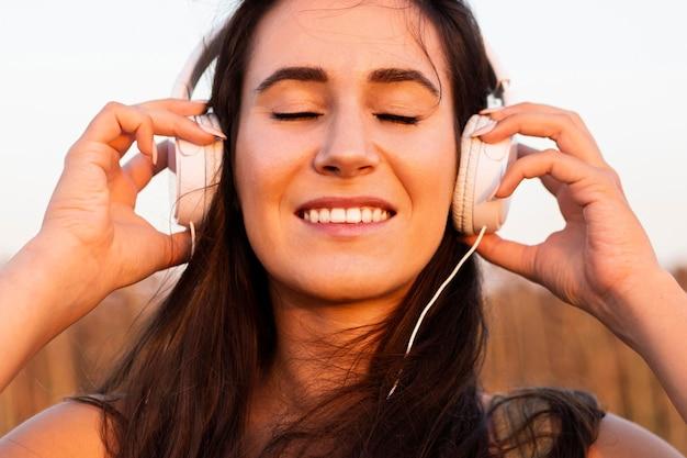 Smiley-frau, die musik draußen in der sonne hört