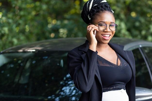 Smiley-frau, die neben auto beim sprechen auf smartphone aufwirft