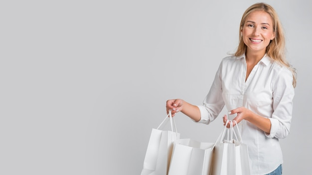 Smiley-frau, die posiert, während einkaufstaschen mit kopienraum halten