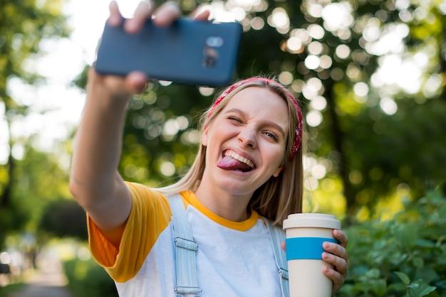 Smiley-frau, die selfie im freien nimmt