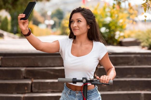 Smiley-frau, die selfie nimmt, während auf roller