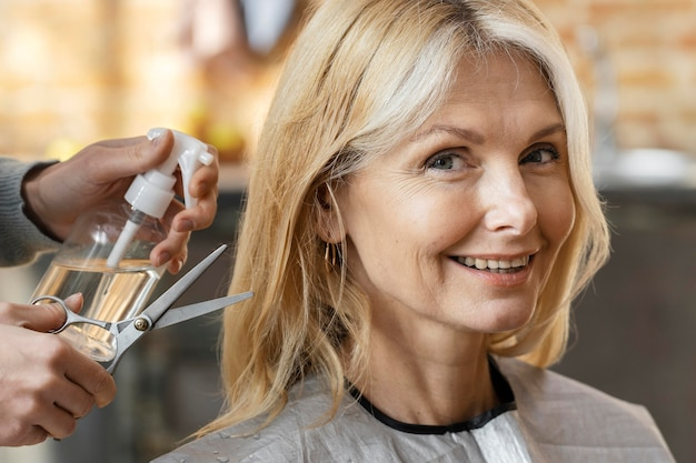 Smiley-frau, die sich für einen haarschnitt zu hause mit friseur bereit macht
