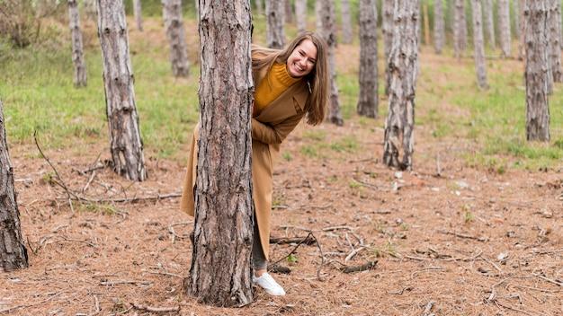 Smiley-frau, die sich hinter einem baum versteckt