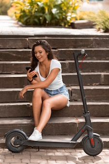 Smiley-frau, die smartphone neben elektroroller verwendet