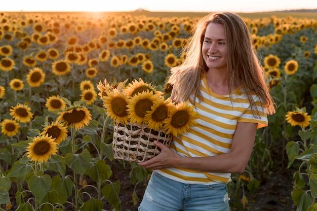 Smiley-frau, die sonnenblumenkorb hält