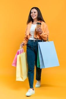Smiley-frau, die tasse kaffee und viele einkaufstaschen hält