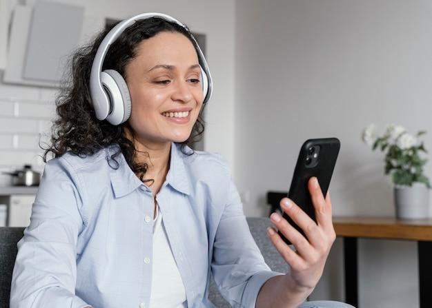 Smiley-frau, die telefon mittlerer schuss hält