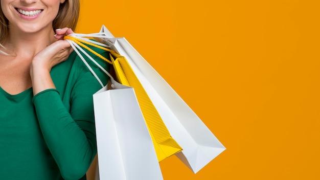 Smiley-frau, die viele einkaufstaschen trägt